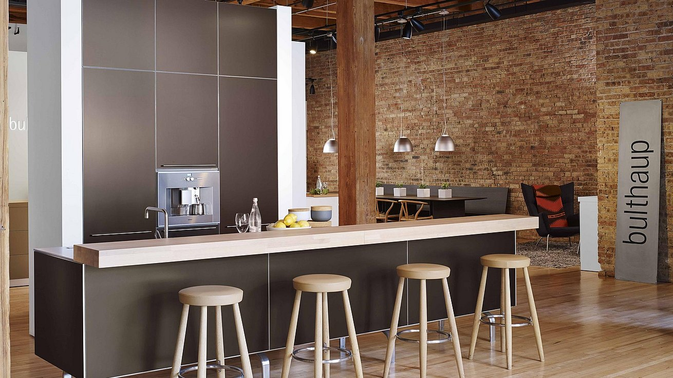 b3 kitchen in bronze anodized aluminum and wide view of showroom featurin exposed brick walls and wood pillars.
