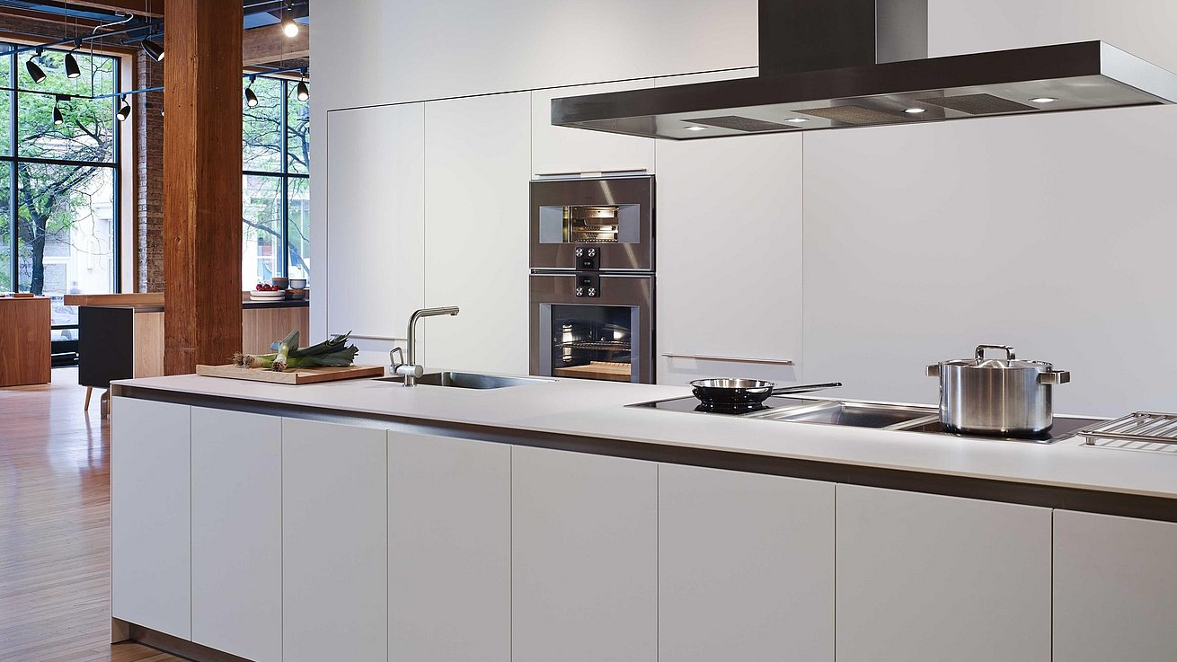 b3 kitchen in white laminate featuring island complete with water point and cooktop.